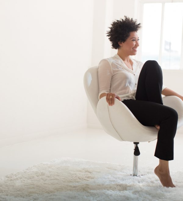 Julia Bullock sits in a white chair, wearing a white blouse and black pants, with one leg folded up on the chair. .