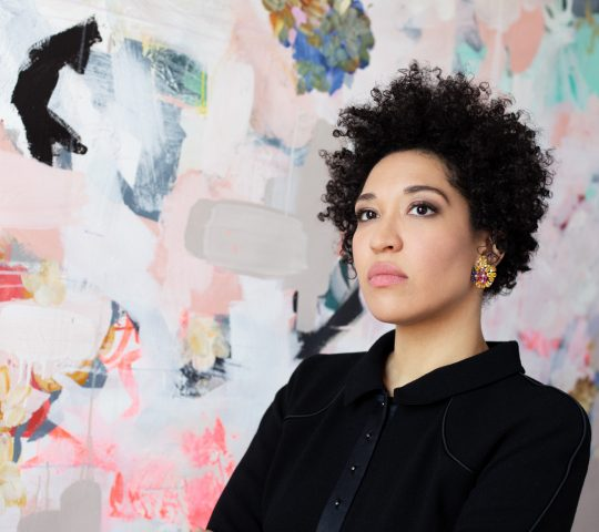 Julia Bullock wears a black blazer, looking of to the side seriously, standing against a backdrop of abstract shapes.