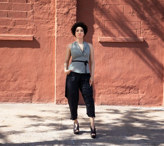 Julia Bullock stands in front of a red brick wall with one hand in her pocket wearing a grey vest with buttons and unstructured black pants.