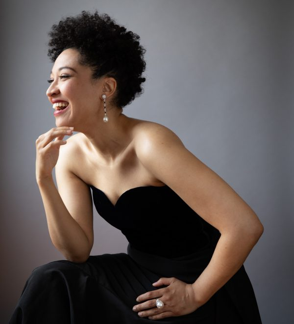 A profile of Julia Bullock, where she wears a black dress, pearl ring and earrings, leaning forward and smiling.