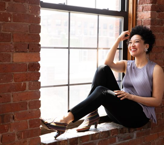 Julia Bullock sits on a red brick window ledge smiling, touching her hair, and wearing a lavender sleeveless blouse, black tapered pants, and crystal and diamond earrings.