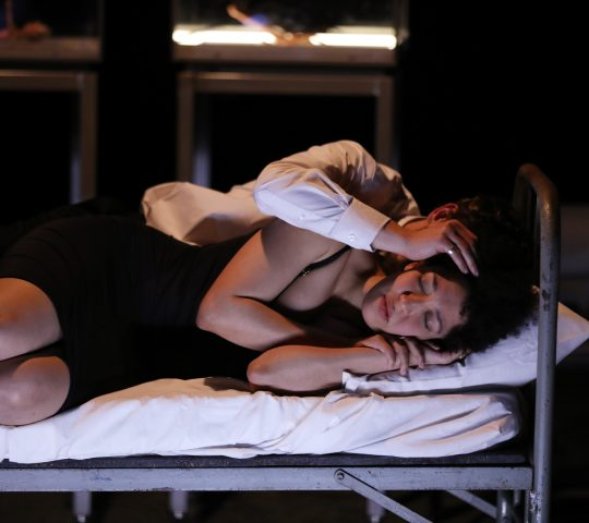 Julia Bullock lays on a bed on stage with a man behind her, his hand covering her ear.