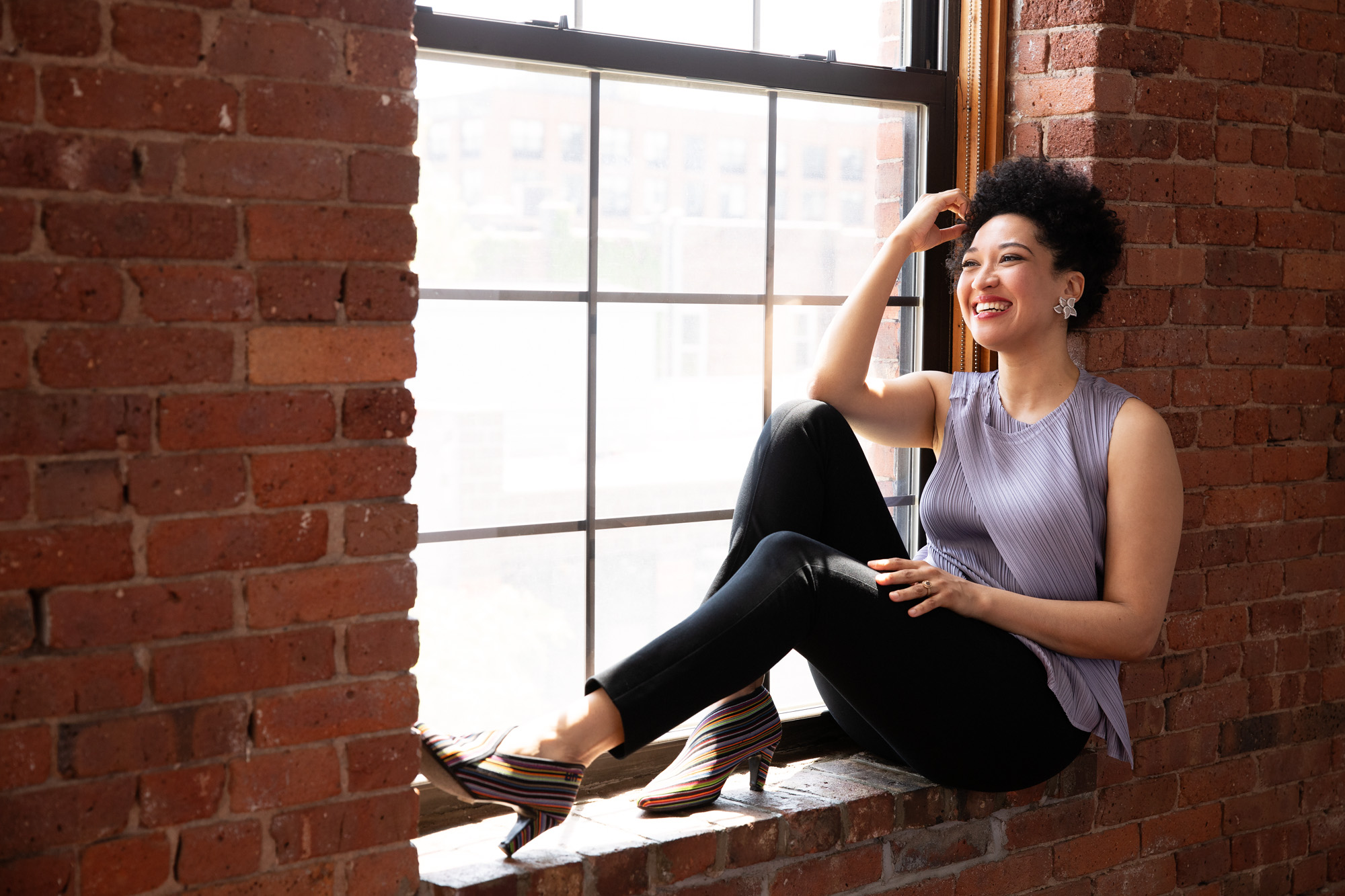 Julia Bullock sits on a red brick window ledge smiling and wearing a lavender sleeveless blouse, black tapered pants, and crystal and diamond earrings.