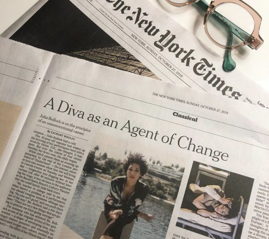 """Julia Bullock's New York Times feature titled, """"A Diva as an Agent of Change"""" on a table along with a pair of pink and green glasses."""