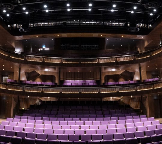A panorama of Lindbury Theatre featuring purple seats and a view of the balconies.